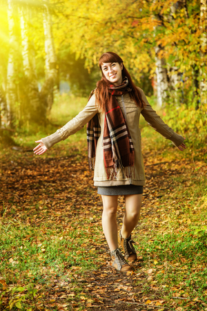 checkered scarf: Cute girl walking in the autumn park Stock Photo