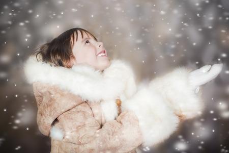 manteau de fourrure: Une petite fille mignonne dans un manteau de fourrure jouit de la neige qui tombe Banque d'images