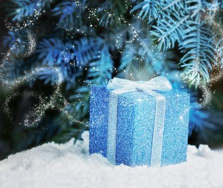 La magia de regalo de la noche de Navidad en la nieve bajo el árbol de Navidad