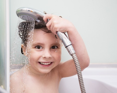 shower stall: Beautiful little girl pours the water from the shower in a bathroom stall
