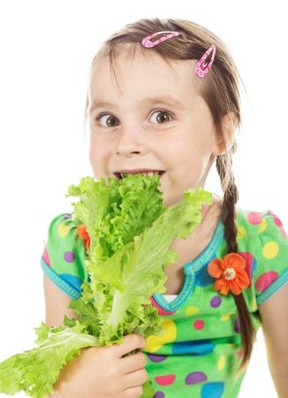 barrettes: Little cute girl bites green leaf lettuce on a white background