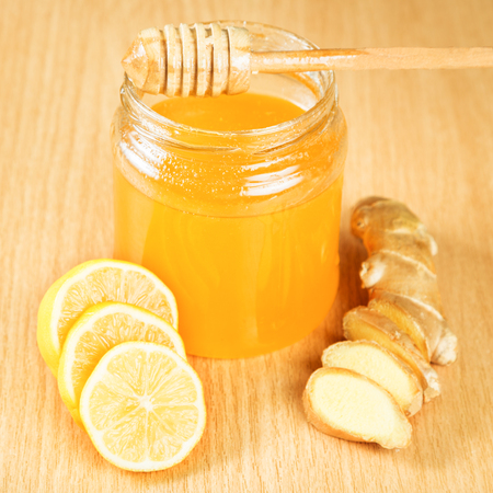 colds: Folk remedies for colds honey, lemon, ginger root on a wooden surface