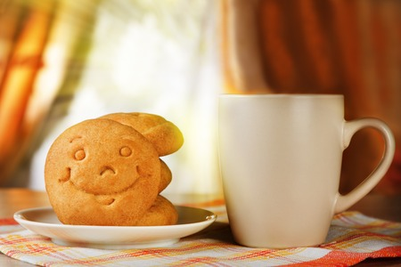 Breakfast for positive mood. A hot drink and biscuit with a smile