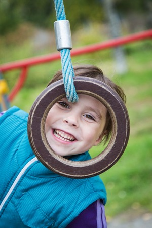 projectile: Cute smiling girl on the playground on the sports projectile ring.