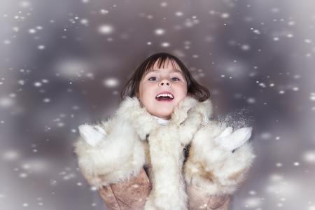manteau de fourrure: Une petite fille mignonne dans un manteau de fourrure jouit de la neige qui tombe sur la nature de fond
