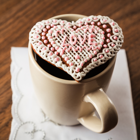 lace pattern: Coffee and cookies in the form of heart on a napkin with embroidery in the form of heart on the background of the wooden table Stock Photo