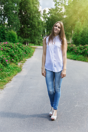 tilted view: Beautiful slim woman walking in the park