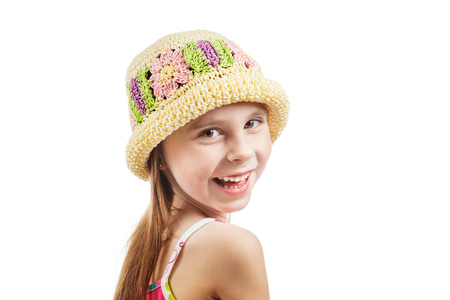 looked: Little girl in a wicker hat looking over her shoulder happily smiling on a white background Stock Photo