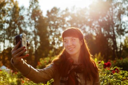 Lovely brunette girl doing selfie in a beautiful garden, backlit Stock Photo