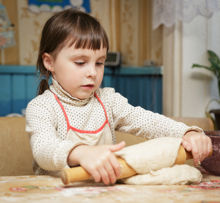 zeal: Little cute girl rolls the dough for baking Stock Photo