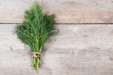 Fresh dill on an old wooden surface