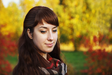 Beautiful girl lowered her eyes down in the autumn park