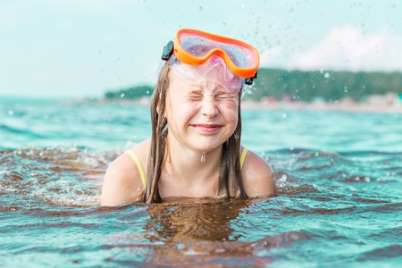 scuba goggles: The girl squeezed her eyes shut from the sea spray swimming in the sea