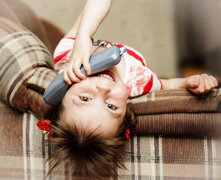Little funny girl lying down talking on a wired phone