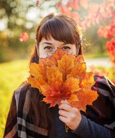 Beautiful red-haired smiling brunette closes face a bouquet of autumn maple leaves