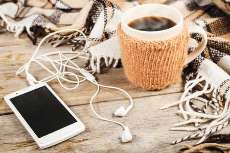 Hot coffee in a large cup, white mobile phone with headphones, checkered plaid on a wooden table surface