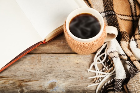 Hot drink in a large cup, book, plaid on a wooden table surface Stock Photo