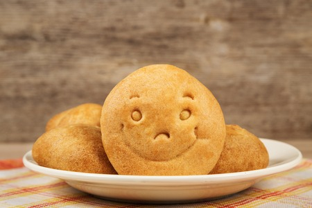 Cookie with a smile on a plate on wooden background texture
