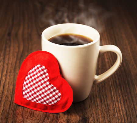 Large cup of hot drink and heart textile on a wooden table surface. The concept of Valentines day holiday