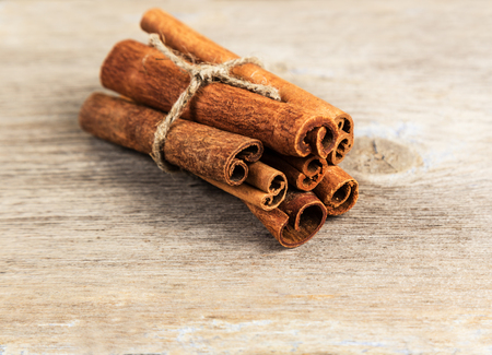 christmas grounds: Cinnamon sticks tied on a wooden surface
