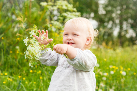 Little cute happy girl in a meadow holding flowers in her hand Stock Photo