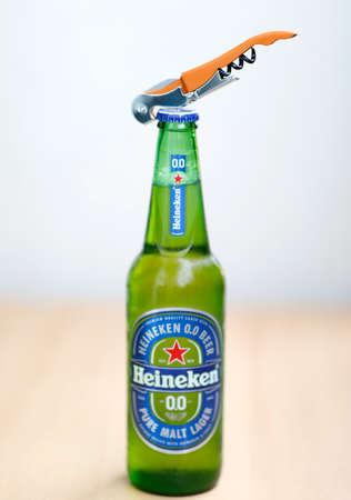 Green glass Heineken beer bottle and bottle opener. September 12, 2020 Warsaw, Poland