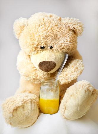 The teddy bear is sitting and eating honey Zdjęcie Seryjne