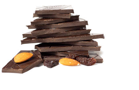 Closeup pieces of dark, inferior chocolate, almonds and raisins on a white background