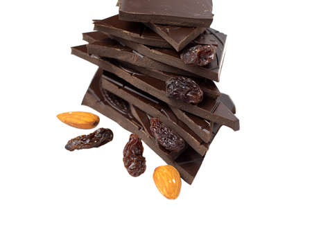 Closeup pieces of dark, inferior chocolate, almonds and raisins on a white background