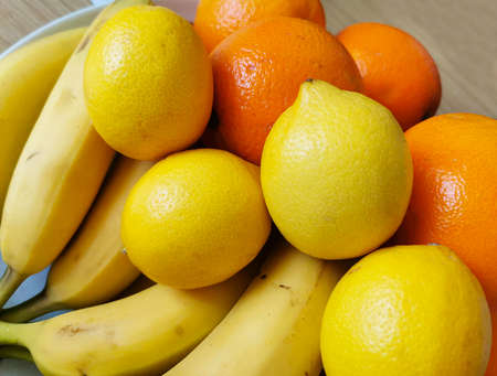 A colorful composition of fresh fruit arranged on a wooden table. The ingredients are: bananas, oranges and lemons