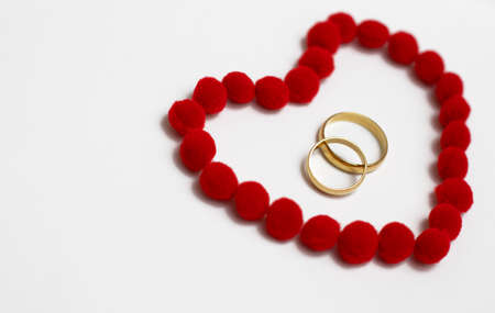 Gold wedding rings in red heart. Wedding rings on the white background, surrounded by the heart. Symbol of love and devotion Zdjęcie Seryjne