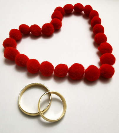 Gold wedding rings and red heart. Wedding rings on the white background, surrounded by the heart. Symbol of love and devotion Zdjęcie Seryjne