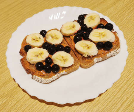 A healthy dessert for breakfast, lunch or dinner dark bread with peanut butter, black currant and banana slices