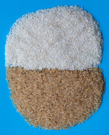 Raw brown and white long rice on a blue background