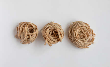 Raw whole grain brown pasta on a white background. Delicate wholemeal pasta made of graham flour, rich in nutrients protein, carbohydrates and fiber
