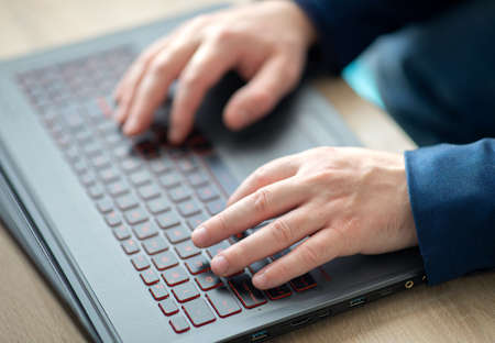 Man's hands typing on a laptop keyboard. A man in an office work writes on a laptop. Selective focus Zdjęcie Seryjne