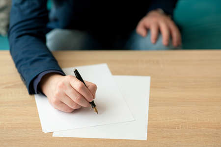 Businessman in the office writes a letter or signs a document on a piece of white paper with a fountain pen with nib. Closeup of hands of a businessman in a suit
