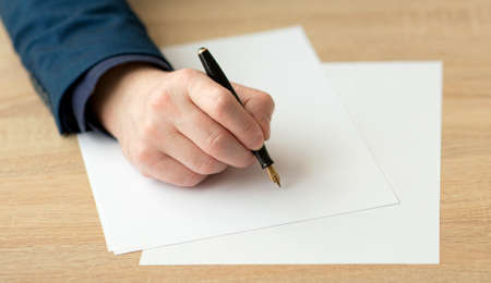 Closeup of hand of a businessman in a suit, writing a letter or signs a document on a piece of white paper with a fountain pen with nib