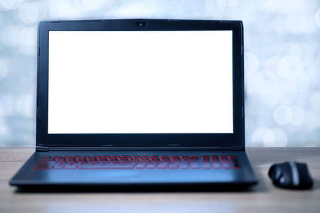 Laptop with blank white screen and wireless mouse on the office table