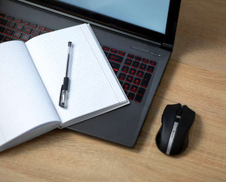 Laptop with wireless mouse, notebook and pen on the office table Zdjęcie Seryjne