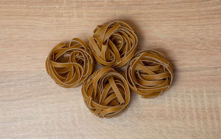 Raw whole grain brown pasta Tagliatelle, made with wheat flour, rich in nutrients: protein, carbohydrates and fiber