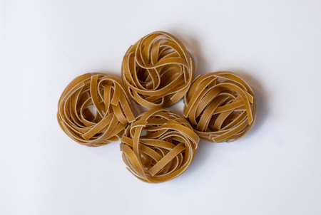 Raw whole grain brown pasta Tagliatelle on a white background, made with wheat flour, rich in nutrients: protein, carbohydrates and fiber