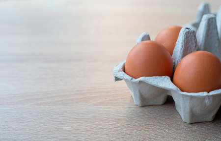 Closeup on carton of three fresh brown free range eggs on a wooden table