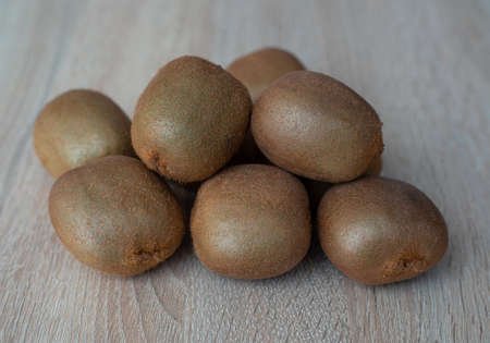 Group of ripe whole green kiwi fruit on a wooden table