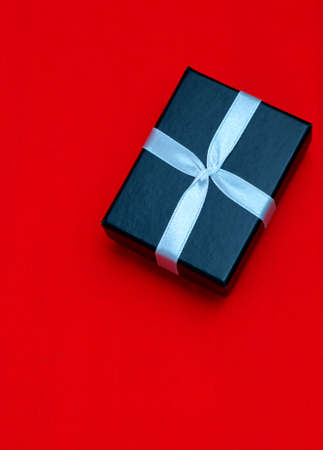 Small rectegular black gift box on a red background, top view