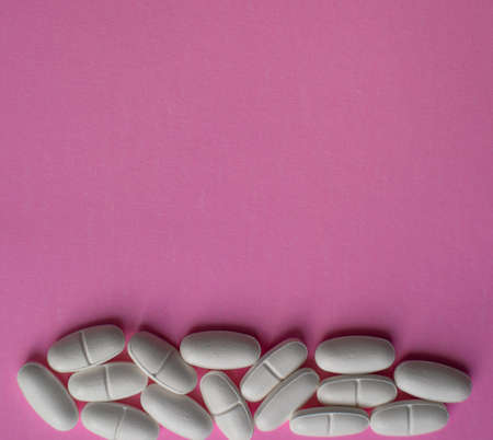 White large pills on a pink background