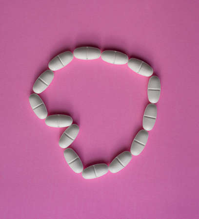 White, large pills or tablets, arranged in a heart shape to represent health on pink background