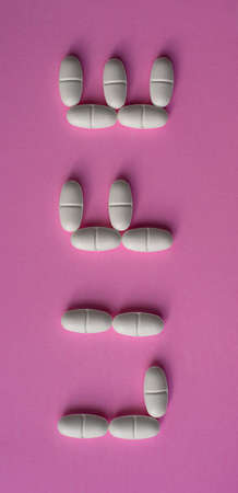 White, large pills or tablets arranged with the text