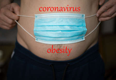 A man holding a blue medical mask over his stomach will gain weight during the pandemic of the coronavirus crisis. Obesity concept Banque d'images