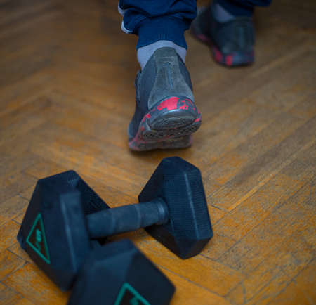 Finished training with weights. Men's sports footwear for exercise, walking or running, and 5 kg dumbbells on a wooden floor Banque d'images